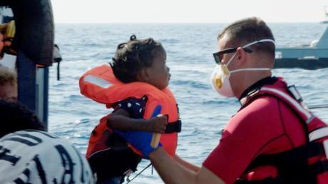 Ein Kind wird vom Seenotrettungsschiff «Alan Kurdi» auf ein Schiff der maltesischen Armee gehoben. Foto: Sea Eye