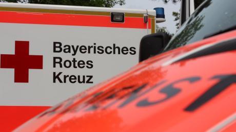 Ein vierjähriger Bub ist am Samstag in Burgau in die Mindel gestürzt und untergegangen. Zwei Männer ziehen den leblosen Körper am Wasserkraftwerk an Land.