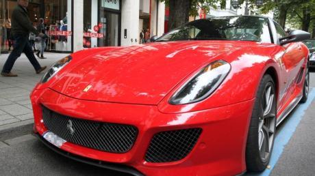 Ein Ferrari parkt auf der Königsallee in Düsseldorf, die als Laufsteg der Reichen und Schönen gilt. Foto: Martin Gerten