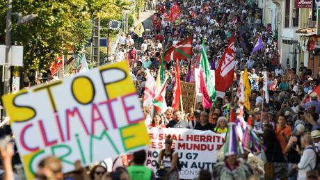 Demonstranten marschieren in Hendaye mit Flaggen und Plakaten während eines Protests gegen den G7-Gipfel.