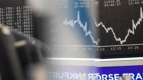 Von jetzt an ohne Thyssenkrupp: Die Dax-Kurve spiegelt sich im Handelssaal der Frankfurter Börse in einem Firmenschild Händlern.