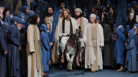 """Der Darsteller Andreas Richter als Jesus (Mitte) reitet in der Szene """"Einzug aus Jerusalem"""" auf einem Esel."""