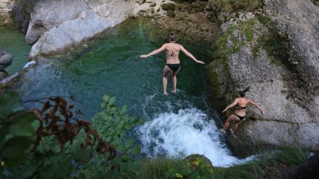 Zwei junge Frauen springen in den Buchenegger Wasserfällen von einem Felsen in eine zehn Meter tiefer gelegene Gumpe.