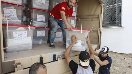Männer verteilen Wahlurnen und Wahlmaterial in Tunis.