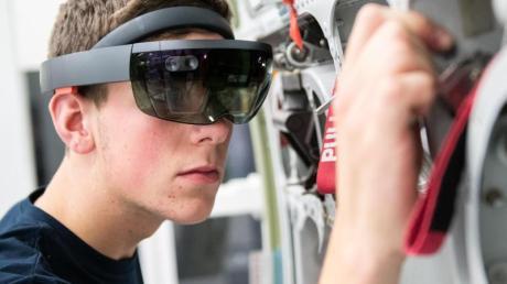 Gesuchter Job mit guten Zukunftschancen: Ein Airbus-Auszubildender arbeitet mit einer Datenbrille an einem Flugzeugbauteil. Foto: Daniel Reinhardt