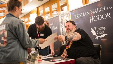 """Schauspieler Kristian Nairn (r.), bekannt als """"Hodor"""" aus der US-Serie «Game of Thrones», überreicht einer Frau eine signierte Autogrammkarte."""