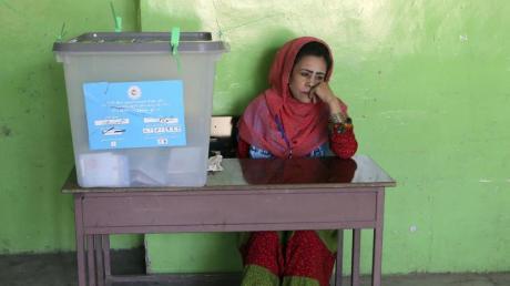 Eine Wahlhelferin sitzt in einem Wahllokal in Kabul neben einer Wahlurne. Foto: Rahmat Gul/AP