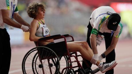 Alina Reh aus Deutschland wird von Helfern mit einem Rollstuhl von der Laufbahn aus dem Stadion gefahren. Sie musste nach 13 von 25 Runden mit Bauchkrämpfen das Rennen pber 10.000 Meter aufgeben.