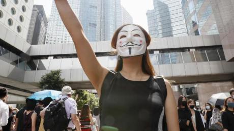 Eine maskierte Frau während einer Demonstration in Hongkong. Foto: ---/kyodo/dpa