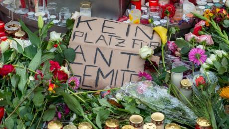 """""""Kein Platz für Antisemiten"""" steht auf einem Pappschild, das auf dem Marktplatz in Halle inmitten von Blumen und Kerzen liegt."""
