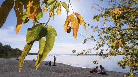 Ausflügler genießen am Ufer des Ammersees unter herbstlich gefärbten Bäumen den Sonnenschein. In den kommenden Tagen wird es in vielen Teilen Deutschlands ungewöhnlich warm. Foto: Karl-Josef Hildenbrand/dpa