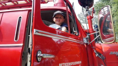 Elias aus Vöhringen sitzt in einem Feuerwehrwagen. Der Siebenjährige will sich seinen Traum verwirklichen und hat sich bei der Berufsfeuerwehr München beworben.