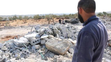 EinMann steht neben den Trümmern eines Hauses in Barischa. In dem Ort in Nordwestsyrien ist nach Angaben von US-Präsident Donald Trump IS-Anführer Abu Bakr al-Bagdadi bei einer amerikanischen Militäraktion getötet worden. Foto: Mustafa Dahnon/dpa