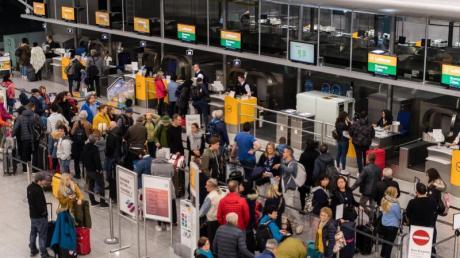 Lange Schlangen vor den Lufthansa-Schaltern am Münchner Flughafen. Foto: Matthias Balk/dpa