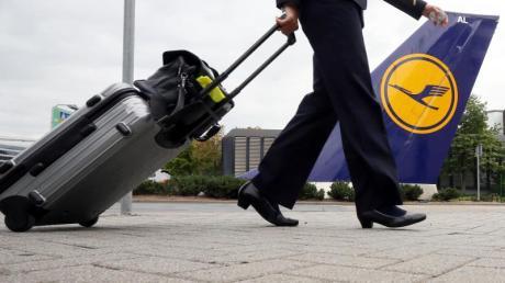 Eine Flugbegleiterin geht auf dem Flughafen in Frankfurt am Main in die Lufthansa-Basis.