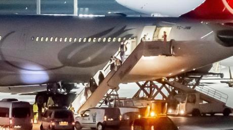 Mitglieder einer Familie steigen am Flughafen Berlin-Tegel aus einem Flugzeug von Turkish Airlines und werden von der Polizei empfangen. Ankara hatte die sieben Personen - darunter ein Baby - abgeschoben; es handele sich um «ausländische Terroristenkämpfer». Foto: Christoph Soeder/dpa
