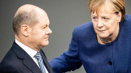 Bundeskanzlerin Angela Merkel (CDU), spricht mit Olaf Scholz (SPD), Bundesfinanzminister, im Bundestag. Foto: Michael Kappeler/dpa