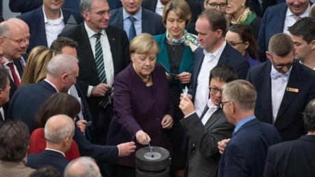 """Bundeskanzlerin Angela Merkel (CDU) und weitere Abgeordnete stimmen bei der 128. Sitzung des Deutschen Bundestages namentlich ab. Debattiert wird der Tagesordnungspunkt """"Klimaschutz"""". Foto: Jörg Carstensen/dpa"""