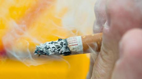 Ein Mann raucht eine Zigarette. Foto: Daniel Bockwoldt/dpa