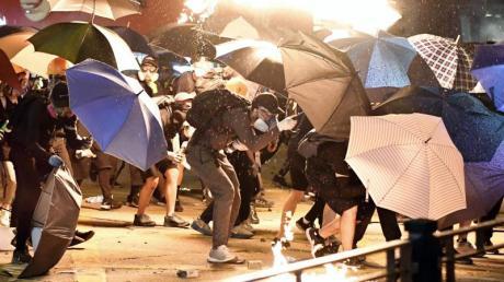 Demonstranten in der Nähe der Hong Kong Polytechnic University suchen Schutz hinter Regenschirmen. Foto: -/kyodo/dpa