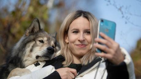 Nicole Lenhardt macht mit ihrem Wolfshund Milo in einem Weinberg ein Selfie.