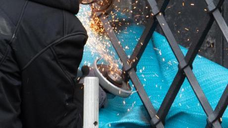 Mitarbeiter einer Restaurierungsfirma arbeiten mit einem Winkelschleifer am durchtrennten Gitterfenster des Grünen Gewölbes.