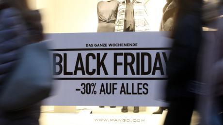Im Schaufenster eines Geschäfts wird für den Black Friday geworben. Schnäppchenjäger rund um den Rabatt-Tag setzen Deutschlands Paketbranche unter Druck.