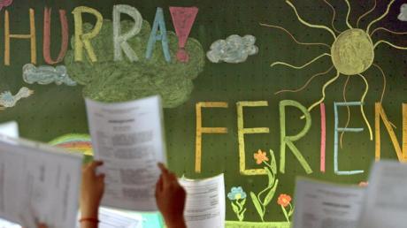 """Kinder der vierten Klasse einer Grundschule in Kaufbeuren jubeln vor einer Tafel mit der Aufschrift """"Hurra Ferien""""."""