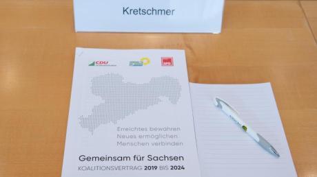 Der Koalitionsvertrag auf dem Platz von Sachsens Ministerpräsident Kretschmer im Landtag.