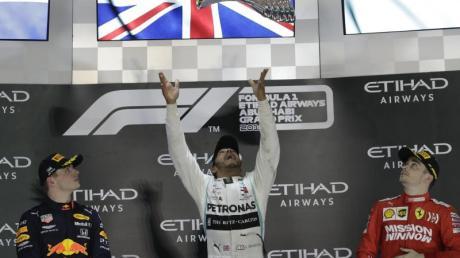 Heute Formel 1, WM-Stand 2019: Endstand Fahrer- und Teamwertung. Abu-Dhabi-Sieger und Weltmeister Lewis Hamilton (M) wirft den Pokal zwischen Max Verstappen (l) und Charles Leclerc in die Höhe.