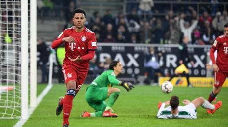Serge Gnabry (l) möchte mit dem FC Bayern München wieder bei Borussia Mönchengladbach jubeln.