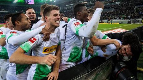 Die Gladbacher Spieler jubeln nach dem Treffer zum 2:1 durch Ramy Bensebaini (r).
