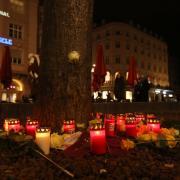 Menschen stellten zum Gedenken an den getöteten Feuerwehrmann am Augsburger Königsplatz Kerzen auf.