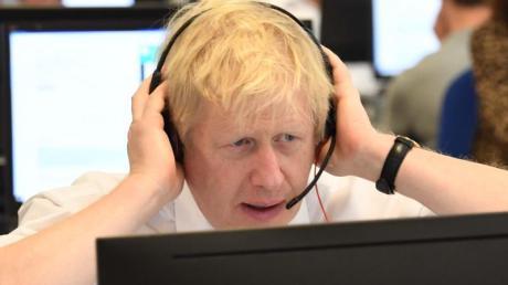 Großbritanniens Premierminister Boris Johnson sitzt mit anderen Kabinettsmitgliedern mit Headset vor einem Bildschirm an einem Tisch im Call Center des Hauptquartiers der Konservativen während des Wahlkampfs.