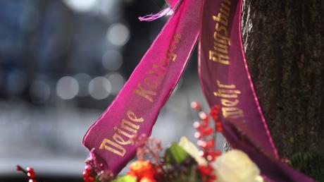 Eine Trauerschleife der Augsburger Feuerwehr ist an einem Baum am Königsplatz befestigt.