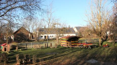 Auf der Wiese hinter der bunten Blockhütte wird die Kinderkrippe gebaut.