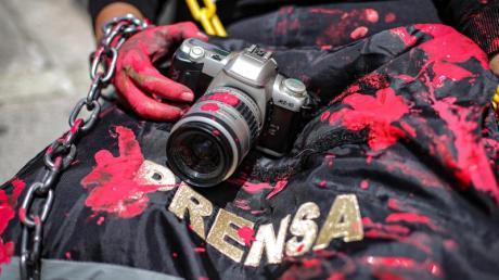 Mit Kamera und rot verschmierter Weste: Mit einer symbolischen Aktion erinnert eine Journalistin in Mexiko an die Ermordung eines Kollegen.
