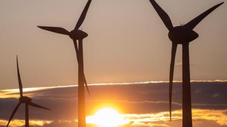 Die Sonne geht hinter Windkraftanlagen unter.