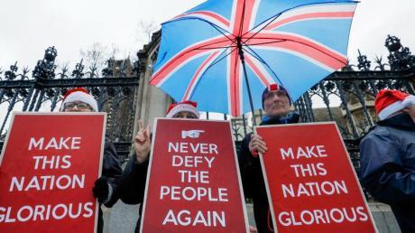 """Befürworter des Brexit halten Plakate mit den Aufschriften """"Never defy the people again"""" (Bietet den Bürgern nie wieder die Stirn) und """"Make this nation glorious"""" (Macht diese Nation prächtig) vor dem britischen Parlament."""