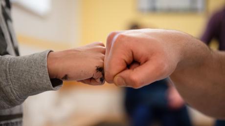 """""""Fist Bump"""" zwischen Vater und Sohn in der JVA Nürnberg: Die Situation von Kindern inhaftierter Eltern spielt in Deutschland bislang keine große Rolle. Das soll sich nun ändern."""
