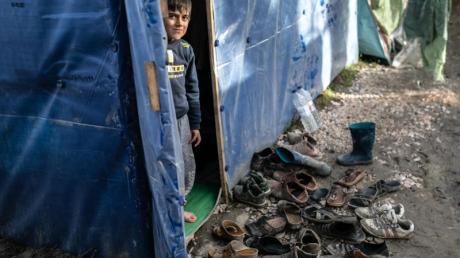 Ein Kind schaut aus einem Zelt im Flüchtlingslager Vial.