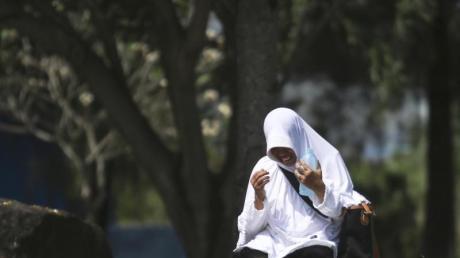 Eine Frau betet an einem Massengrab für die Opfer des Tsunami im Indischen Ozean in Banda Aceh.
