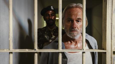 """Martin Endler (Siemen Rühaak) wird von einem Gefängniswärter (Komparse) in seine Zelle geführt. Szene aus dem München-Tatort """"One Way Ticket"""", der heute im Ersten lief."""