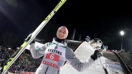 Karl Geiger jubelt mit dem silbernen Pokal für seinen zweiten Platz.