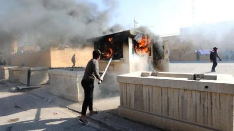 Ein Demonstrant schürt vor der Botschaft der Vereinigten Staaten in Bagdad ein Feuer.
