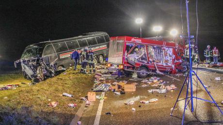 Feuerwehrleute stehen neben einem zerstörten Kleinlaster und einem Reisebus. Beim dem Zusammenprall sind beide Fahrer tödlich verunglückt. Im Bus wurden zwei weitere Personen schwer verletzt, wie die Polizei weiter mitteilte.