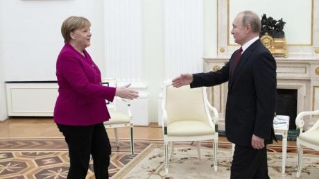 Kanzlerin Angela Merkel und der russische Präsidenten Wladimir Putin begrüßen sich vor den Gesprächen über die Krisenherde im Nahen und Mittleren Osten im Kreml.