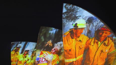 Als Dank und Zeichen der Solidarität werden Bilder von Feuerwehrleuten auf die großen Segel der Oper in Sydney projiziert.