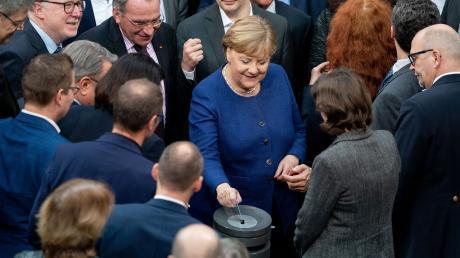 Bundeskanzlerin Angela Merkel gibt bei der Sitzung des Bundestages ihre Stimmkarte bei der namentlichen Abstimmung über neue Organspende-Regeln ab.
