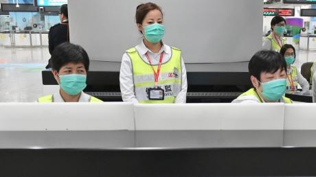Mitarbeiter des Honkonger Gesundheitswesens untersuchen am Bahnhof West Kowloon Station Reisende auf ihren Gesundheitszustand.